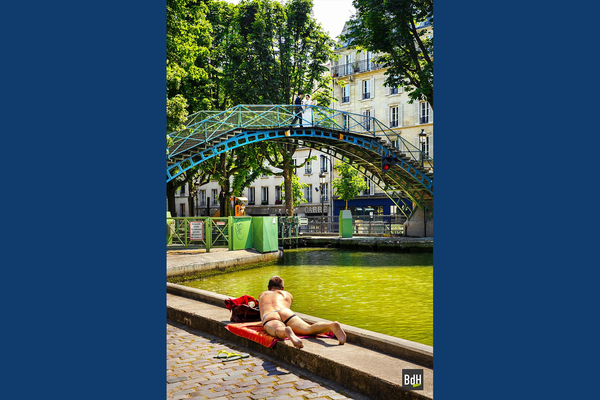 Couple asiatique de mariés se faisant prendre en photo sur la passerelle Bichat devant un homme nu bronsant allongé sur le bord du Canal Saint-Martin, Paris, France